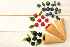 Mix of blueberries, blackberries, raspberries in ice cream cone on light wooden table. Background. top view with copy space Royalty Free Stock Photo