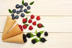 Mix of blueberries, blackberries, raspberries in ice cream cone on light wooden table background. top view with copy space stock photography
