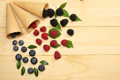 Mix of blueberries, blackberries, raspberries in ice cream cone on light wooden table background. top view with copy space stock images