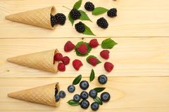 Mix of blueberries, blackberries, raspberries in ice cream cone on light wooden table background. top view with copy space royalty free stock image
