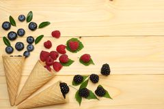 Mix of blueberries, blackberries, raspberries in ice cream cone on light wooden table background. top view with copy space royalty free stock photography