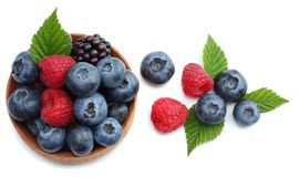 Mix of blueberries, blackberries, raspberries in wooden bowl isolated on white background. top view Stock Photo