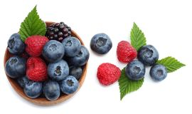 mix of blueberries, blackberries, raspberries in wooden bowl isolated on white background. top view stock image