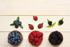 Mix of blueberries, blackberries, raspberries in wooden bowl on light wooden table background Stock Photography