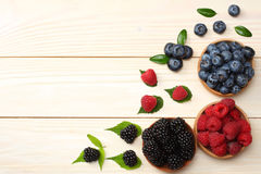 Mix of blueberries, blackberries, raspberries in wooden bowl on light wooden table background Stock Photos