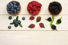 Mix of blueberries, blackberries, raspberries in wooden bowl on light wooden table background Stock Images
