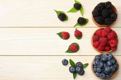 mix of blueberries, blackberries, raspberries in wooden bowl on light wooden table background. top view with copy space royalty free stock images