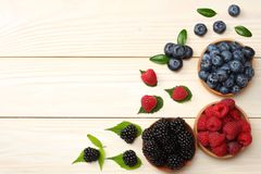 Mix of blueberries, blackberries, raspberries in wooden bowl on light wooden table background. top view with copy space stock photo