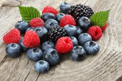 Mix of blueberries, blackberries, raspberries in wooden bowl on old wooden table background. stock image