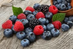 mix of blueberries, blackberries, raspberries in wooden bowl on old wooden table background. stock photography