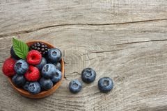 Mix of blueberries, blackberries, raspberries in wooden bowl on old wooden table background. top view with copy space stock photo