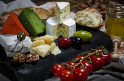 Mix cheese on dark background on wood board with grapes, honey, nuts, tomatoes and basil. Top view. royalty free stock photography