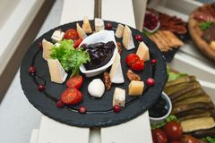 Mix cheese on wooden board with tomatos royalty free stock photography