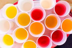 Mix of children drinks in white plastic cups from above. Yellow, red, orange royalty free stock photography