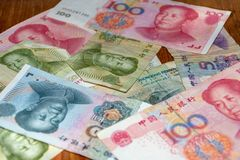 A mix of Chinese Renminbi RMB or Yuan Currency Bills spread out on the table stock image