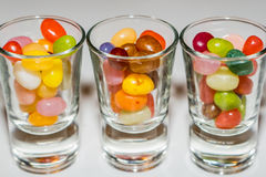 A mix of colored jelly beans candy in shot glasses. A mix of colored jelly beans candy in shot glasses on a white background Royalty Free Stock Images