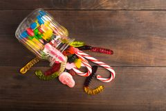 Mix colorful candies in glass jar in wooden background Royalty Free Stock Image