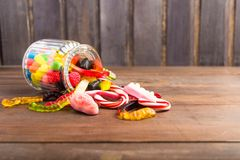 Mix colorful candies in glass jar in wooden background Stock Photos
