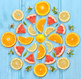 Mix of colorful citrus fruit on blue background. Pattern of mix fresh sliced ​​citrus on blue wooden surface royalty free stock photography