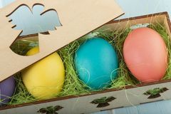 Mix of colorful Easter chicken eggs in a wooden box royalty free stock photo