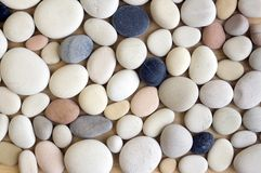 White pebbles background, simplicity, daylight, stones. Mix colors pebbles background, simplicity, daylight, stones, spread on wooden background, one by one Royalty Free Stock Image