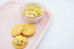 Mix corn, oats and sweetened condensed milk put on cracker. Placed on pink tray with white background Stock Images