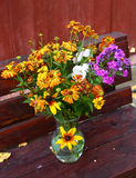 Mix country flower bouquet on the wooden bench Royalty Free Stock Photo