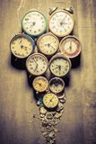 Mix of damaged clocks in pile. On wooden table Royalty Free Stock Image