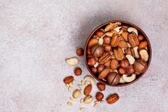Mix of different nuts. Mix of nuts in a wooden bowl on a light background. view from above stock image