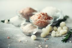 Mix of different salt types on grey concrete background. Sea salts, black and pink Himalayan salt crystals, powder. Rosemary. Salt crystal balls from Dead sea royalty free stock image