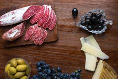 Mix of different snacks and appetizers. Spanish tapas on a wooden plate. Tapas bar. chorizo, olives, sausage, cheese,grape. Top vi. Mix of different snacks and royalty free stock photography
