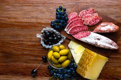 Mix of different snacks and appetizers. Spanish tapas on a wooden plate. Tapas bar. chorizo, olives, sausage, cheese,grape. Top vi. Mix of different snacks and stock photography