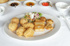 Mix Dim Sum Fried. Dim sum mix have Deep fried stuffing mashed soybean, Deep fried taro, Deep fried squid and Fried turnip cake in white plate at restaurant with Stock Images