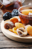 Mix of dried fruits with cup of black tea Royalty Free Stock Photo