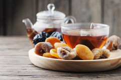 Mix of dried fruits with cup of black tea Stock Images