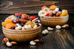 Mix of dried fruits and nuts on a dark wood background with copy space. Symbols of judaic holiday Tu Bishvat. Mix of dried fruits and nuts on dark wood royalty free stock photography