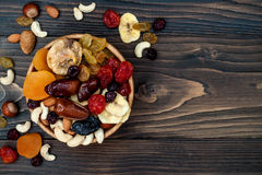 Mix of dried fruits and nuts on a dark wood background with copy space. Top view. Symbols of judaic holiday Tu Bishvat. Stock Image