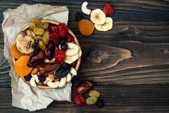 Mix of dried fruits and nuts on a dark wood background with copy space. Top view. Symbols of judaic holiday Tu Bishvat. Royalty Free Stock Image
