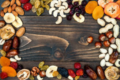 Mix of dried fruits and nuts on a dark wood background with copy space. Top view. Symbols of judaic holiday Tu Bishvat. Royalty Free Stock Photo