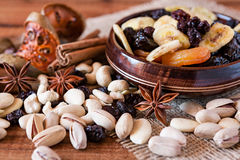 Mix of dried fruits and nuts. Mix of dried fruits in a wooden bowl and nuts over a rustic table Royalty Free Stock Photography