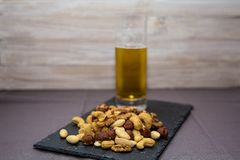 Mix Of Dry Fruits On a Slate Board, With a Glass Of Beer on a Wooden Background stock image