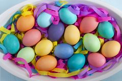 Mix of dyed bright Easter eggs in a dish with colorful paper ribbons royalty free stock images
