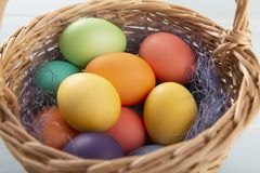 Mix of dyed bright Easter eggs in a withe basket with colorful blue sisal royalty free stock image
