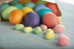 A mix of Easter bright dyed chicken eggs in a paper bag on a table stock images
