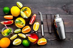 Mix exotic fruit cocktail with alcohol. Shaker and strainer near citrus fruits and glass with cocktail on dark wooden. Background top view stock photo