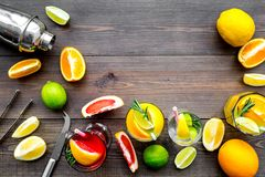 Mix exotic fruit cocktail with alcohol. Shaker and strainer near citrus fruits and glass with cocktail on dark wooden. Background top view stock image