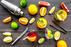 Mix exotic fruit cocktail with alcohol. Shaker and strainer near citrus fruits and glass with cocktail on dark wooden. Background top view royalty free stock photos