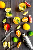 Mix exotic fruit cocktail with alcohol. Shaker and strainer near citrus fruits and glass with cocktail on dark wooden. Background top view royalty free stock photo