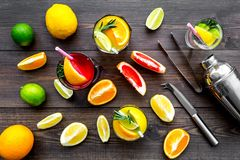 Mix exotic fruit cocktail with alcohol. Shaker and strainer near citrus fruits and glass with cocktail on dark wooden. Background top view stock images