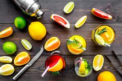 Mix exotic fruit cocktail with alcohol. Shaker and strainer near citrus fruits and glass with cocktail on dark wooden. Background top view royalty free stock images